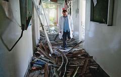 DESTRUIÇÃO Um médico inspeciona os danos causados a um hospital de Zawia, a oeste de Trípoli, atingido pelos combates  (Foto: Bob Strong/Reuters )