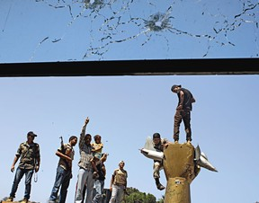 CENAS DE UMA GUERRA Combatentes celebram a vitória em monumento erguido por Khadafi contra os EUA (Foto: Sergey Ponomarev/AP)