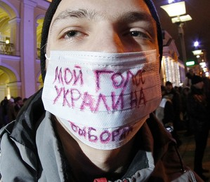 """Jovem protesta nas ruas de São Petersburgo contra Vladimir Putin e o resultado das eleições russas.  Na máscara: """"Meu voto foi roubado nas eleições"""" (Foto: Dmitry Lovetsky)"""