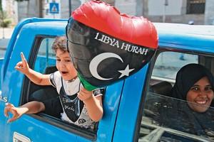 CELEBRAÇÃO Família comemora nas ruas de Trípoli a queda de Muammar Khadafi, após seis meses de revolução e conflito. O movimento nasceu após revoluções bem-sucedidas na Tunísia e no Egito (Foto: Francois Mori/AP)