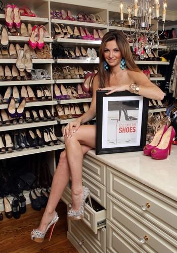 A jogadora profissional de poker e blogueira Beth Shak posa ao lado de sua coleção de 1.200 pares de sapatos, avaliada em R$ 2 milhões (Foto: Reprodução Internet)