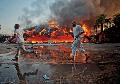 CONQUISTA Líbios correm diante de incêndio no quartel-general de Muammar Khadafi, em Trípoli. Na semana anterior à tomada da capital, aliados do ditador ainda faziam uma festa no local (Foto: Bryan Denton/The New York Times)