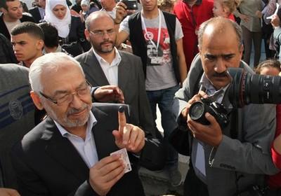 Rachid Ghannouchi, líder do An-Nadha, exibe o dedo sujo de tinta (usada para identificação do eleitor) ao deixar a votação em Menzeh, cidade próxima a Túnis, capital da Tunísia (Foto: Amine Landoulsi / AP)