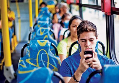 Jovem usa celular durante trajeto de ônibus: 250,8 milhões de linhas ativas (Foto: Reprodução Internet)