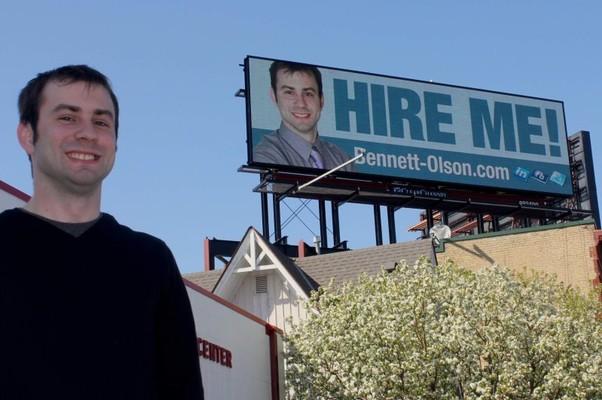 Bennett Olson, ao lado do outdoor que mostrar sua foto e seu pedido desesperado por emprego (Foto: Facebook)