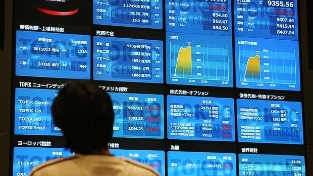Investidor observa o painel de cotações da Bolsa de Tóquio Economia do Japão (Foto: Getty Images)