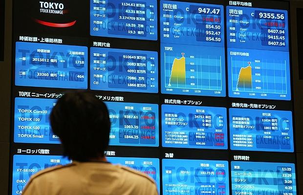 Investidor observa o painel de cotações da Bolsa de Tóquio (Foto: Getty Images)