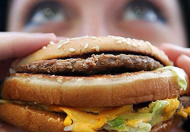 Jovem come hamburguer em lanchonete Fast food Junk food (Foto: Getty Images)