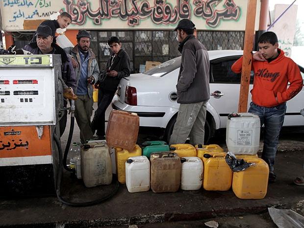 Palestinos fazem fila durante horas para encher barris com combustível: abertura para desempregados (Foto: Getty Images)