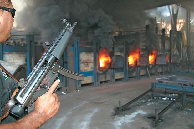 COMBATE Umagente da PF vigia incineração de drogas em São José do Rio Preto, São Paulo. O orçamento de repressão ao tráfico diminuiu (Foto: Carlos Chimba)