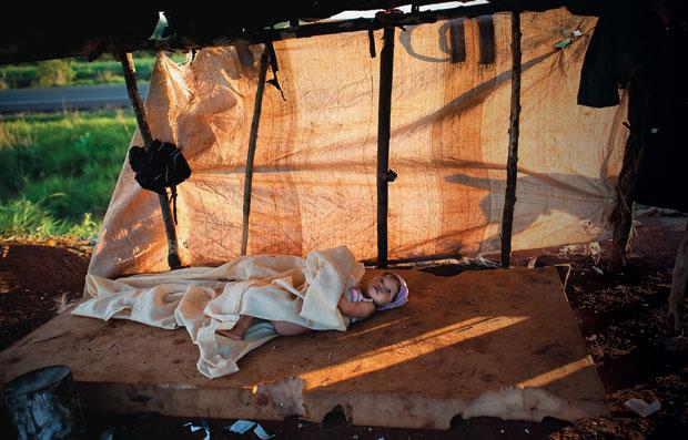 ESPERA A índia Sandriele, da etnia guarani-caiová, num dos barracos do acampamento Apikay, na estreita faixa entre a BR-463 (ao fundo) e a cerca  de um canavial. Há anos sem nenhuma atividade, sua família só sobrevive das doações de cestas básicas  (Foto: Filipe Redondo )