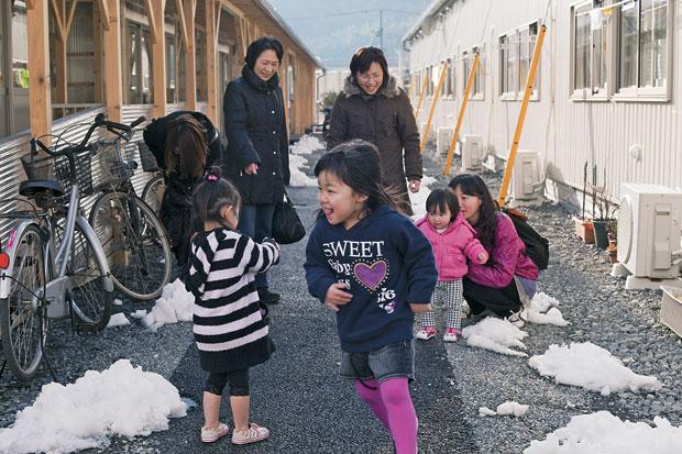 RECOMEÇO  Kimio Shirakawa (de casaco marrom) observa as netas Riona e Runa (em primeiro plano) brincando com uma amiga (de rosa).  Elas tentam retomar a vida numa casa construída pelo governo em Ishinomaki após o tsunami  (Foto: Hitoshi Katanoda)