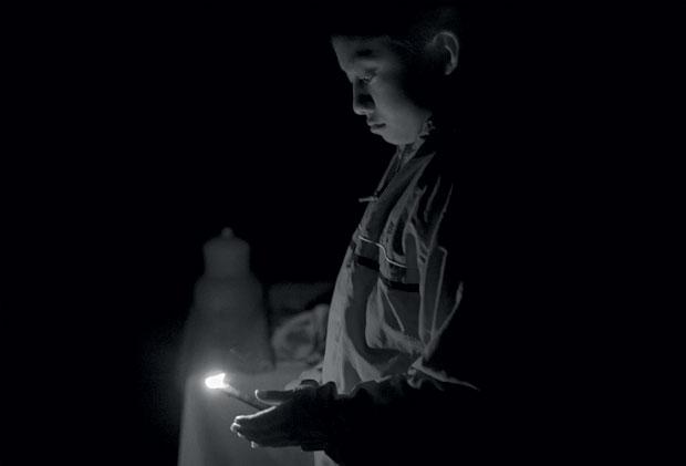 Ainda no escuro, às 5 e meia da manhã, Diego, de 9 anos, se prepara para acender a fogueira do ritual do kiili'ich k'á, como oferenda aos deuses (Foto: Adriana Zehbrauskas )