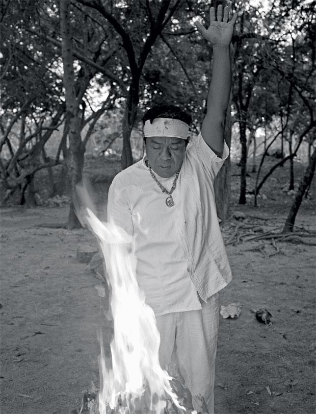 O ápice da cerimônia. Com os primeiros raios da manhã, o sacerdote Tiburcio Can May ora diante da fogueira no meio de um sítio arqueológico, em Mérida (Foto: Adriana Zehbrauskas )