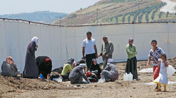 ARIDEZ Na fronteira com a Turquia, refugiados sírios armazenam água em potes. A seca    prolongada arruinou a agricultura do país e criou um cenário de tensão social (Foto: Umit Bektas/Reuters)