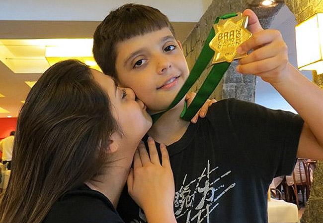 A atriz paparica o menino, que exibe sua medalha de ouro (Foto: Reprodução/Bloglog)