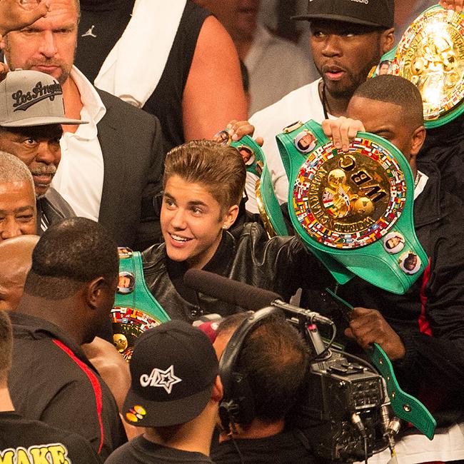 Justin Bieber segura os cinturões de Mayweather. Ao fundo, o rapper 50 Cent (Foto: Grosby Group)