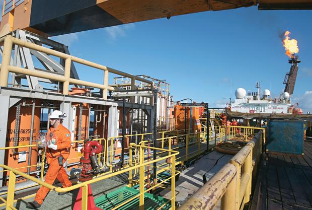 RIQUEZA NATURAL Um funcionário da Petrobras explora o primeiro campo no pré-sal. O petróleo que gera empregos, mas também altera o clima da Terra (Foto: Wilton Juni0r/AE)