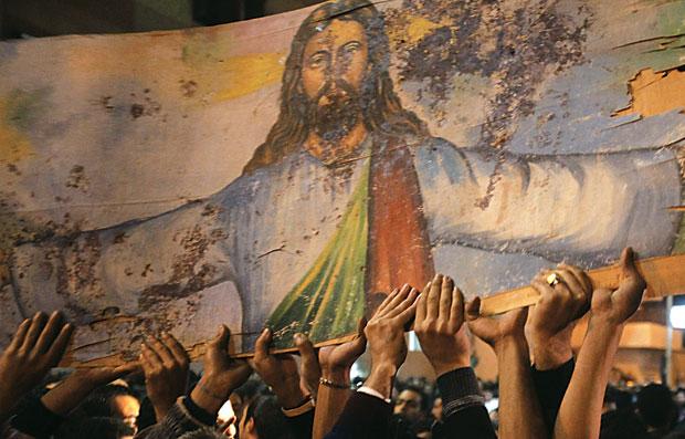 Cristãos coptas, do Egito, carregam uma imagem de Jesus Cristo manchada de sangue, em ato contra a violência de extremistas islâmicos (Foto: Asmaa Waguih/Reuters)