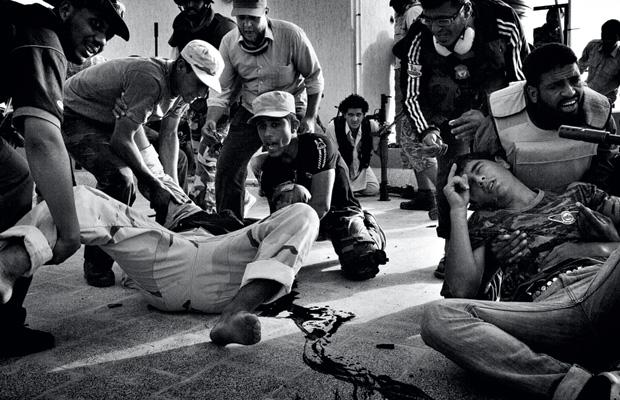 9 de outubro de 2011 Jovens rebeldes da cidade de Misurata atiram contra forças leais ao coronel Khadafi do terraço de um edifício residencial na zona leste de Sirte, na Líbia. Muitos foram feridos sob as lentes de Lima (Foto: Maurício Lima)